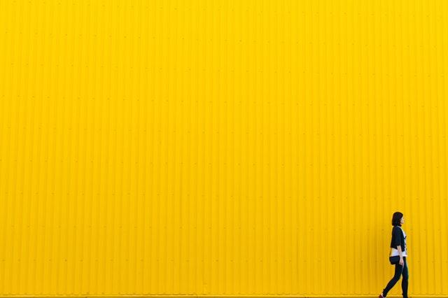 nő sétál sárga fal előtt