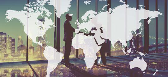 világtérkép mögött kezet fogó emberek